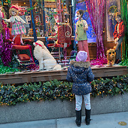 A little girl stops to look at the Saks 5th Avenue window displays for the Holiday season during the Coronavirus (Covid-19) outbreak in Manhattan,New York on Sunday, December 6, 2020. (Alex Menendez via AP)