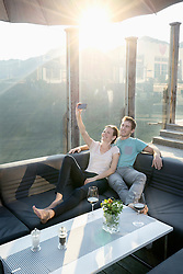 Young couple taking selfie with smartphone on terrace and smiling, Zillertal, Tyrol, Austria
