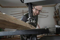 Male bow maker sawing wood with a bandsaw, Bavaria, Germany