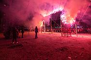 Pirotécnicos comienzan la quema de un castillo mientras el público contempla el espectáculo. Feria Internacional de la Pirotecnia 2020.  /  Pyrotechnicians performing at the Pyrotechnics International Fair 2020.