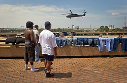 30 August, 2005. New Orleans Louisiana. Hurricane Katrina aftermath. <br /> Evacuees from the floods dry their clothing and watch helicopters landing and taking off from the makeshift medical facilities outside the Superdome. Approximately 20,000 storm evacuees are housed at the Superdome.<br /> Photo Credit: Charlie Varley/varleypix.com