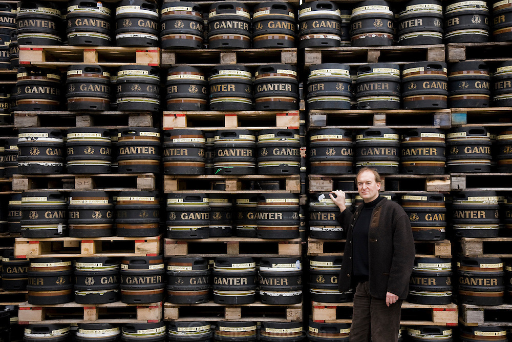 """Brewmaster Joachim Rösch stands next to barrels of beer at the Ganter Brewery in Freiburg im Breisgau, Germany.  (Joachim Rösch  is featured in the book What I Eat: Around the World in 80 Diets.)  The caloric value of his day's worth of food in March was 2700 kcals. He is 44 years of age; 6 feet, 2 inches tall; and 207 pounds. Joachim's job requires him to taste beer a number of times during the week, and unlike in wine tasting, he can't just taste then spit it out: """"Once you've got the bitter on the back of your tongue, you automatically get the swallow reflex, so down the chute you go,"""" he says. MODEL RELEASED."""