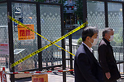 Salarymen, wearing surgical masks, walk past a smoking area in the street which has been closed with tape to ensure social distancing during the COVID-19 State of Emergency in Tokyo Shinjuku, Tokyo, Japan. Thursday May 7th 2020. The month-long state of emergency declared by the Japanese government in response to the COVID-19 pandemic was due to end on May 7th but was extended to May 31st despite Japan appearing to have avoided the high infection and mortality rates of some countries. Areas like Shibuya have many businesses shuttered and closed and the streets are a lot quieter than usual.