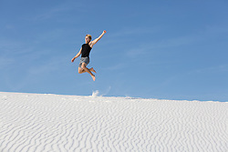 athletic man on a sand dune leaping in mid air