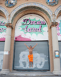 Shirtless man in a towel jumping in front of a closed down building in Coney Island, NY