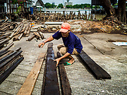 16 AUGUST 2017 - BANGKOK, THAILAND: A man scavenges used construction wood left behind after city officials tore down several homes built on pilings in the Wat Thewarat Kunchorn community. The community is one of the 14 riverside communities that will be torn down to make way for a riverfront promenade. Construction of the 14 kilometer long promenade will start in late 2017.           PHOTO BY JACK KURTZ