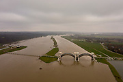 Nederland, Gelderland, Nijmegen, 04-002-2021; Hoog wNederland, Gelderland, Gemeente Overbetuwe, 04-002-2021; Hoog water bij de stuw bij Driel in de Neder-rijn. In verband met het hoge water ten gevolge van overvloedige regenval en smeltwater bij de bovenloop van de rivier de Rijn, heeft ook de benedenloop - de Nederrijn - met hoge waterstanden te maken. Daarom is de vizierschuif van de stuw is geopend. De stuw bij Driel, de Kraan van Nederland, zorgt voor afvoer van het water van de Rijn via Nederrijn en Lek.<br /> High water at the weir at Driel in the Lower Rhine. Due to high waters caused by abundant rainfall and meltwater at the upper coures of the river Rhine, the Lower Rhine also has to deal with high water levels. Therefore, the visor slide of the weir has been opened. The weir at Driel, the Kraan van Nederland, provides drainage of the water from the Rhine via Nederrijn and Lek.<br /> drone-opname (luchtopname, toeslag op standaard tarieven);<br /> drone recording (aerial, additional fee required);<br /> copyright foto/photo Siebe Swart