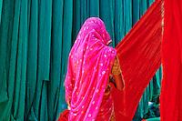Inde, Rajasthan, Usine de Sari, Santosh, 30 ans. Les tissus sechent en plein air. Ramassage des tissus secs par des femmes et des enfants avant le repassage. Les tissus pendent sur des barres de bambou. Les rouleaux de tissus mesurent environ 800 m de long. . // India, Rajasthan, Sari Factory, Santosh, 30 old. Textile are dried in the open air. Collecting of dry textile  are folded by women and children. The textiles are hung to dry on bamboo rods. The long bands of textiles are about 800 metre in length.