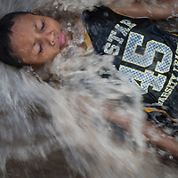 Jaffet Quesada Murillo, 9, plays in fast-flowing flood waters in San Pedro Sula after hurricanes Eta and Iota devasted housing and crops in the area.<br /> <br /> Photograph taken with his mother's verbal consent.