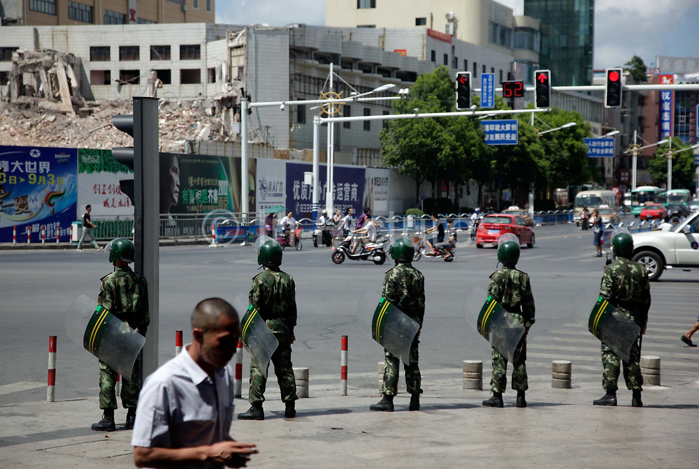 Riot police carrying batons and shields stand guard near the municipal government offices in Qidong, Jiangsu Province, China on 31 July 2012. Thousdans of prostesters took to the street of Qidong, a small city some 100 KM north of Shanghai, after they heard a Japanese paper plant is building a waste water outlet near their estuary.