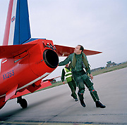 Pilot of the Red Arrows, Britain's RAF aerobatic team performs a pre-flight check before training flight. Flt. Lt. Si Stevens of the elite 'Red Arrows', Britain's prestigious Royal Air Force aerobatic team, walks around his  Hawk jet at RAF Scampton, Lincolnshire. He will fly up to 6 times daily during this winter training, when weather permits, learning new manoeuvres. Wearing winter green flying suits, their day is spent flying and de-briefing. Stevens wears a green flying suit with anti-g pants and helmet on with its pilot number. He is being followed by a member of the team's support ground crew who outnumber the pilots 8:1. The engineer wears a fluorescent yellow tabard and stands politely by the waiting aircraft on the 'line'. He has already prepared it for flight and helps with any technical issues that may arise.