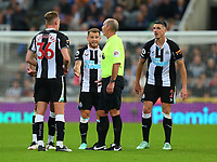 NEWCASTLE UPON TYNE, ENGLAND - SEPTEMBER 17: Newcastle players show their annoyance to the referee, Mike Dean, during the Premier League match between Newcastle United and Leeds United at St. James Park on September 17, 2021 in Newcastle upon Tyne, England. (Photo by MB Media)