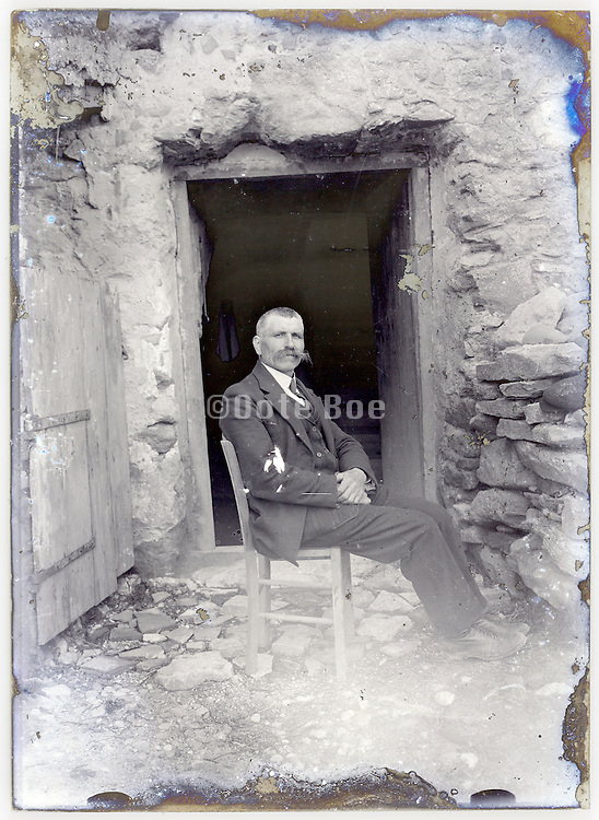 eroded glass plate with an adult man sitting in front of open door