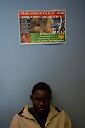 A blind man from Zimbabwe seats under a poster of demonstration pro Zimbabweans human rights.