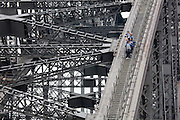 """BridgeClimb participants and guide on the Sydney Harbour Bridge, Sydney, Australia.The Sydney Harbour Bridge is a steel through arch bridge across Sydney Harbour that carries rail, vehicular and pedestrian traffic between theSydney central business district (CBD) and the North Shore. The dramatic view of the bridge, the harbour, and the nearby Sydney Opera House is an iconic image of both Sydney and Australia. The bridge is locally nicknamed """"The Coathanger"""" because of its arch-based design...The bridge was designed and built by Dorman Long and Co Ltd, Middlesbrough Teesside and Cleveland Bridge, Darlington, County Durham and opened in 1932. Until 1967 it was the city's tallest structure.[citation needed] According to Guinness World Records, it is the world's widest long-span bridge and it is the tallest steel arch bridge, measuring 134 metres (440 ft) from top to water level. It is also the fifth-longest spanning-arch bridge in the world."""