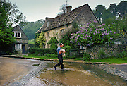 Farmer carrying lamb across a ford at Duntisbourne Lear, Gloucestershire, United Kingdom