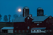 Chester, New York - The nearly full moon rises  behind Brookview Farm on March 22, 2016.