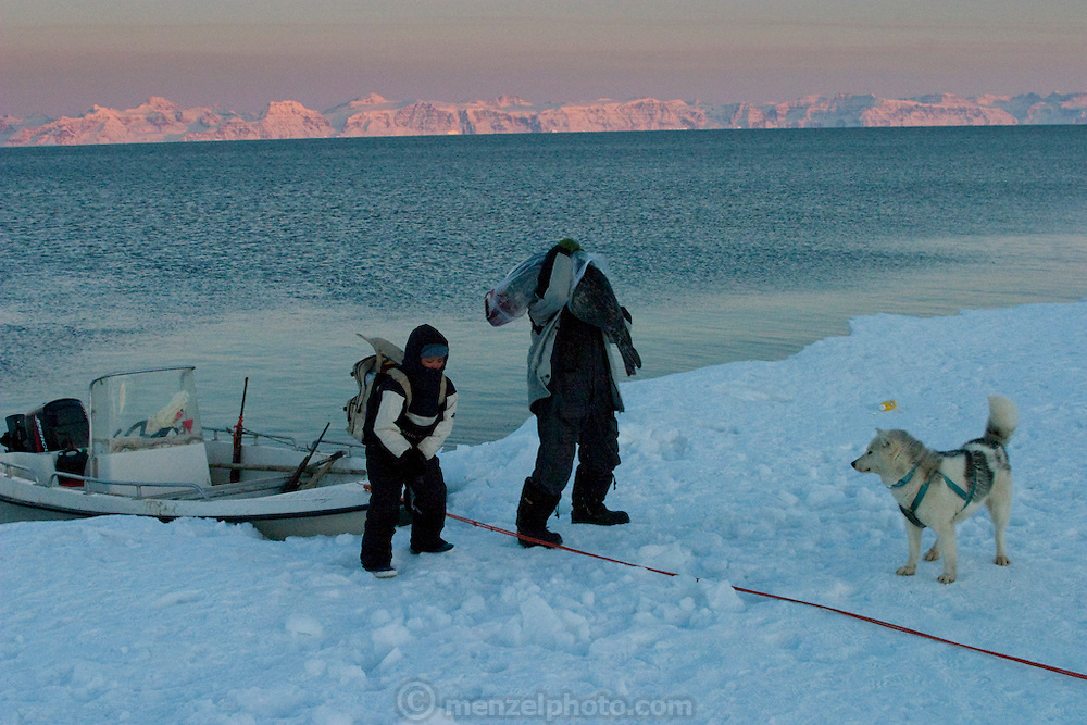 Seal hunter Emil Madsen (right) carries a seal after a day of hunting in Cap Hope Village, Greenland. (Emil Madsen is featured in the book What I Eat: Around the World in 80 Diets.)