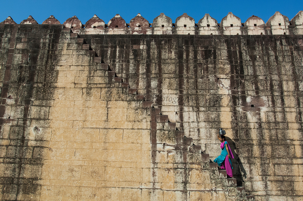 Woman carrying water up steps of the wall surrounding Mehrangarh Fort of Jodhpur. Rajasthan, INDIA<br /> This is one of the most impressive fortresses in rajasthan. Perched on top of a rocky cliff 400 feet above the plain, it has a commanding view of the surrounding area. The fort itself is divided broadly into 3 areas: the outer court, with its old stables and kitchens, the Durbar hall, reception rooms and maharajas palaces and finally the zenana, or queen's palaces. The palace complex constructed around a series of interconnecting courtyards and adorned with breathtaking carved sandstone filigree was first built in 1459 and added to over the centuries. <br /> The Kingdom of Jodhpur was established in the 12th century but in the 15th century the fort and city walls were constructed and they still stand today. Jodhpur is the second largest city in Rajasthan with a population of 1.3 million. Jodhpur may be called the 'Blue City' from the characteristic pale indigo colour of its traditional homes. Originally the color signified the home of the Jodhpuri Brahmin but the copper sulphate in the paint seems to ward off termites and mosquitos so many people then followed the traditional of painting their homes blue. The very narrow streets are filled with colourful bazaars where merchants are selling their wares.