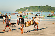 Myanmar, Ngapali. Men carry empty canisters.<br /> Every single morning all the fisherman from the little village at Ngapali Beach come back home with their night catch. At the beach all the women wait for them and afterwards work with drying and selling fish and other creatures from the sea begins.