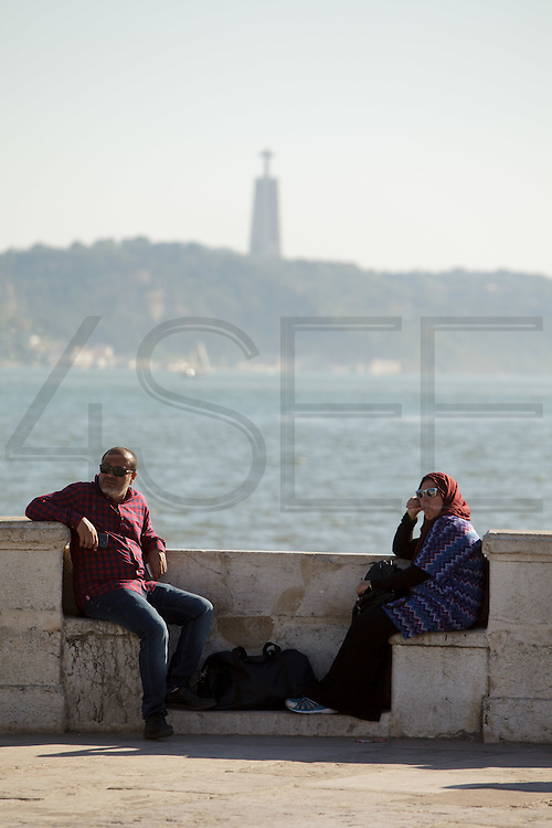 People enjoying the sun at Cais das Colunas (Columns Pier) by the Tagus riverside. The pier is part of Terreiro do Paço, the largest Lisbon square, and is one of the most well-know place to visit in Lisbon.