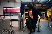 Heathrow Express passenger struggles through barrier in Heathrow train station at Heathrow's terminal 3.