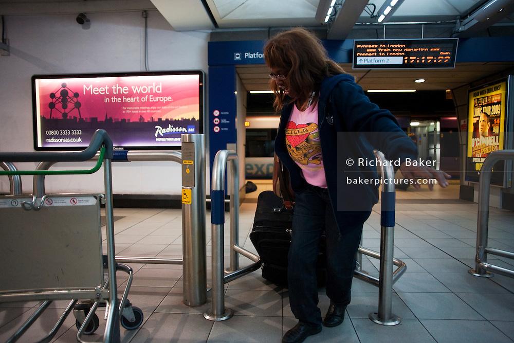Heathrow Express passenger struggles through barrier in Heathrow train station at Heathrow's terminal 3.