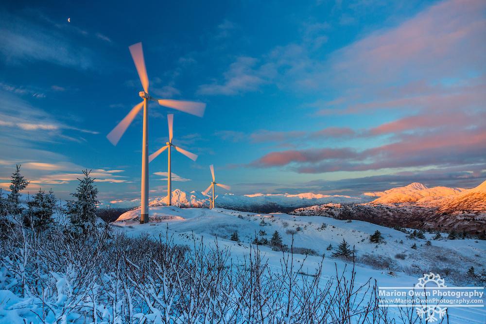 Sunrise light up wind turbines harvesting winter wind near Kodiak, Alaska.