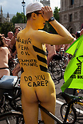 People with painted slogans against oil and vehicle emissions at the World Naked Bike Ride taking place in London. A peaceful, imaginative and fun protest against oil dependency and car culture. A celebration of the bicycle and also a celebration of the power and individuality of the human body. A symbol of the vulnerability of the cyclist in traffic. The world's biggest naked protest: 50+ cities and thousands of riders participate worldwide, including around 1500 in London.