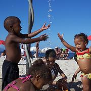 Young children play with a beach shower at Copacabana beach, Rio de Janeiro,  Brazil. 4th July 2010. Photo Tim Clayton..