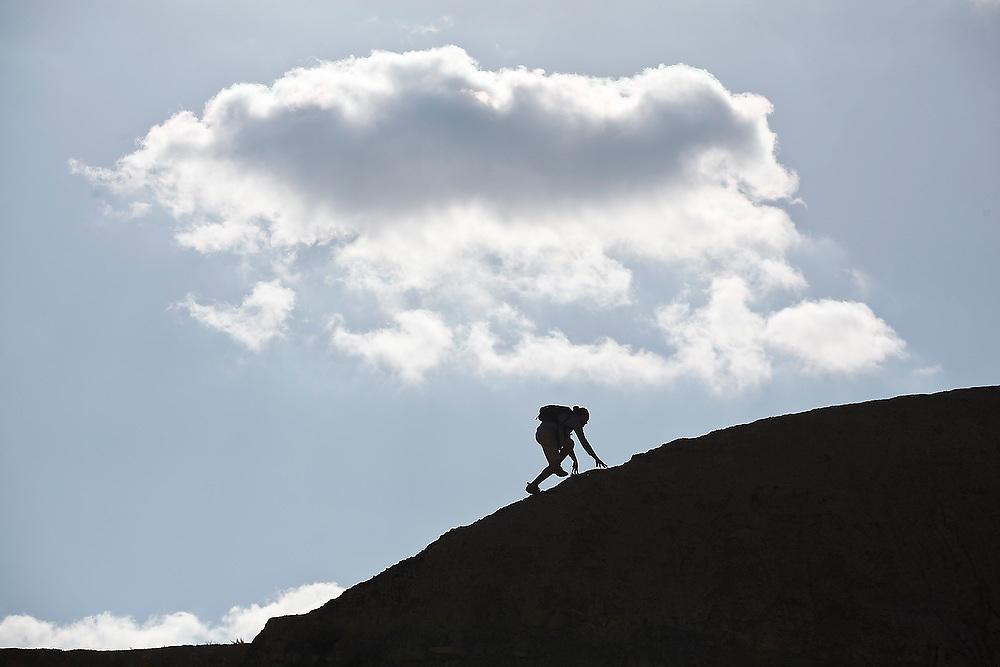 A young man scrambles over mancos shale badlands near Factory Butte, Utah.