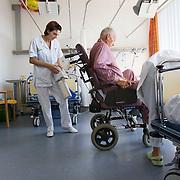 Nederland Rotterdam  31-08-2009 20090831 Foto: David Rozing .Serie over zorgsector, Ikazia Ziekenhuis Rotterdam. afdeling cardiologie, oudere man wordt in rolstoel geholpen, via een slangetje in zijn neus krijgt hij extra zuurstof toegediend, de verpleegster achter hem draagt de  zuurstoftank. Older patient is helped by nurses into a wheelchair, in his nose is a tube for providing oxygen. The nures behind hem carries the oxygen tank.  heartdecease. ..Foto: David Rozing ..Holland, The Netherlands, dutch, Pays Bas, Europe, hart- en vaatziekten, 6 minuten, op zaal liggen,ziektekosten,,zorgverlening,hartziekte, hartklachten, hartziekten, hart en vaten, vaatziekten, hartfalen, hartspierziekte, hartinfarct, hartaanval, hartritmestoornis, hartspier, heart, heart rate monitor, hartslagmonitor, medical science, pijn op de borst, slangetjes,ongezond,oud ,ouderen, op leeftijd zijn, oude van dagen, heartfailure, cardiac arrest, heart attack, ronde doen, routine verpleegkundigen, op zaal liggen, hulp, helpen,, nursing, aansterken,handeling, handelingen, mobiliteit,lopen,ziektekosten,zorgverlener, zorgverleners,zorgverlening, hartpatient, heartpatient