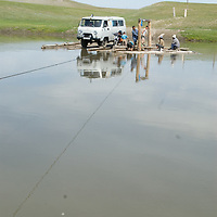 MONGOLIA. Members of an archaeology expedition pull wooden ferry across a river between Rinchenlhumbe and Tsaagan Nuur.
