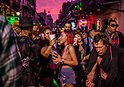 Partying on Bourbon Street during the evening of Mardi Gras on 25th February 2020 in New Orleans, Louisiana, United States. Mardi Gras is the biggest celebration the city of New Orleans hosts every year. The magnificent, costumed, beaded and feathered party is laced with tradition and  having a good time. Celebrations are concentrated for about two weeks before and culminate on Fat Tuesday the day before Ash Wednesday and Lent.