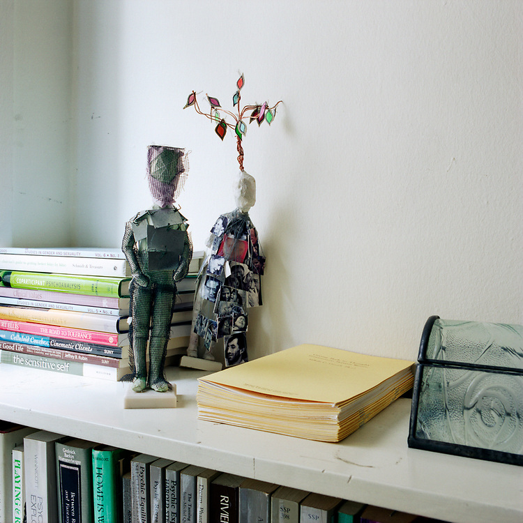 Two figurine sculptures on a bookcase, one with a wire coming out of its head with colorful diamonds hanging from it. There are some books to the left and some manilla files and a glass container on the right.