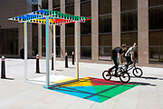 Cyclists pedal past the artwork entitled 4 Colours at 3 Meter High by Daniel Buren leaves multi-coloured patterns from strong sunlight  on the pavement at One Creechurch Place, on 17th Juy 2017, in the City of London, England.