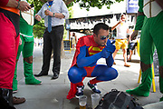 Superman lights up a cigarette as stag party friends dressed up in superhero costumes start their stag do along the Southbank in London, UK. This is a right of passage style gathering where the objective is to have fun, be a little silly, and drink a considerable amount of alcohol.
