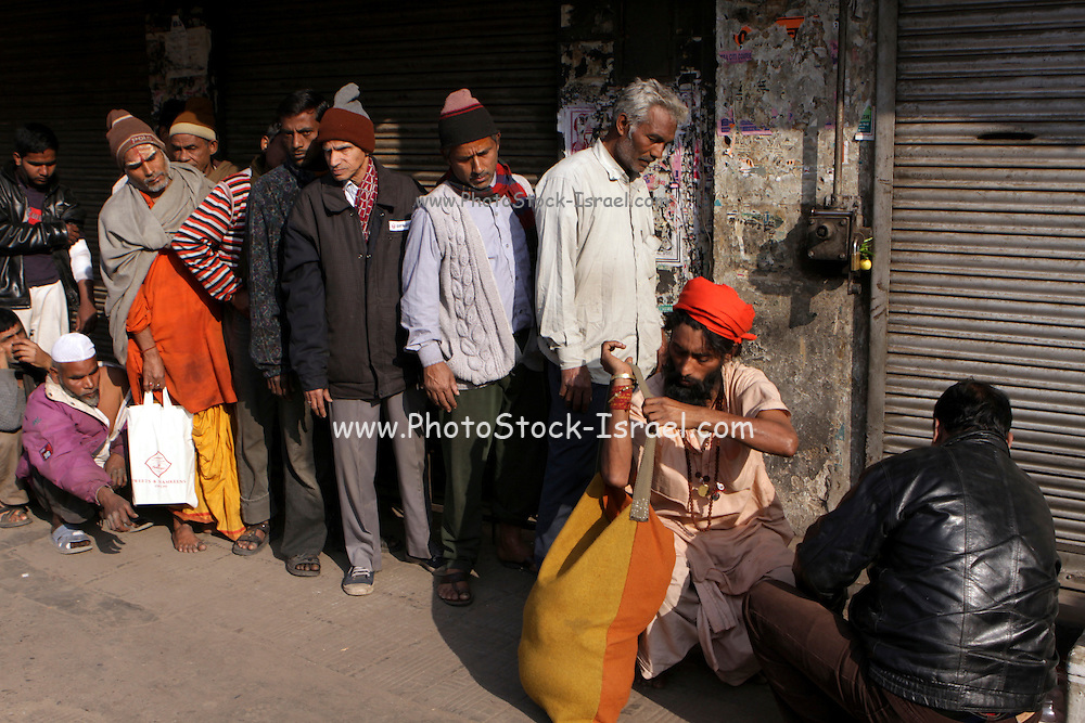 India, National Capital Territory of Delhi Man is vaccinated in the street