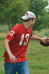 Teenager enjoying running with a football out in a field