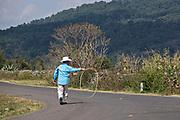 A Mexican cowboy walks down a rural road practicing his lasso skills outside Cucuchucho, Michoacan, Mexico.