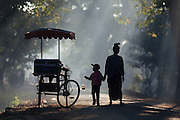Mother and child walking past candy cart and child hold a toy, Thandwe