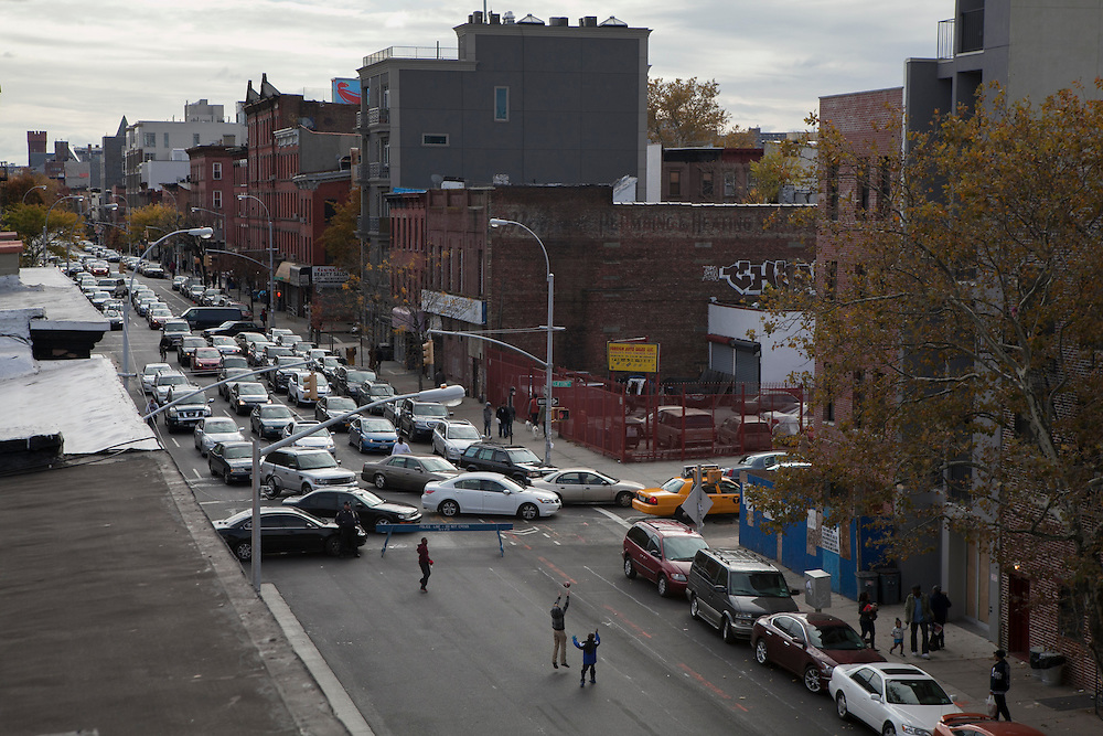 Kids play football in Bedford Ave in Bed-Stuy as the street is closed for participants in the New York City Marathon in Brooklyn, NY on Sunday, Nov. 3, 2013.<br /> <br /> CREDIT: Andrew Hinderaker for The Wall Street Journal<br /> SLUG: NYSTANDALONE