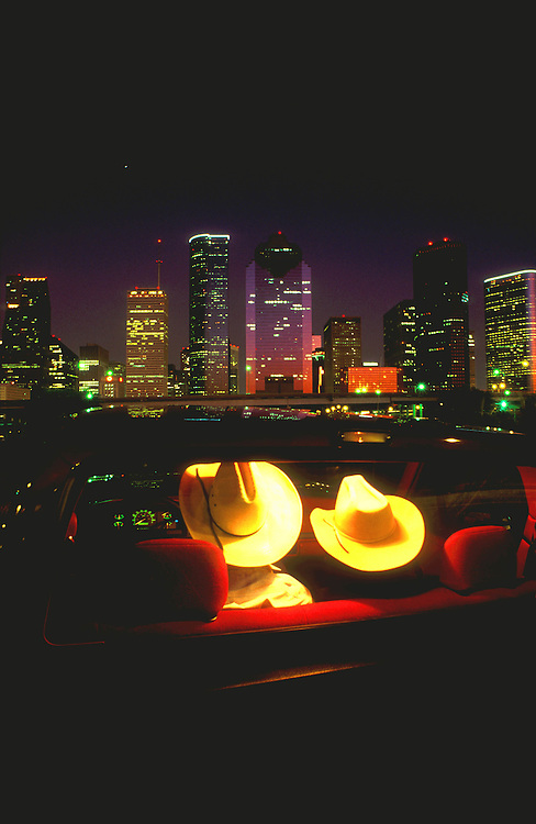 A couple in cowboy hats looking at downtown Houston, Texas skyline at night.