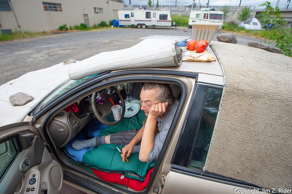 A homeless woman is forced to live in her car in a parking lot on the near east side of downtown Portland, Oregon.
