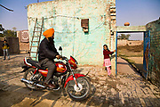 Jasbir Kaur opens the gate of the family home to allow her father to head to work, Chita Kalaan village, Punjab, India.