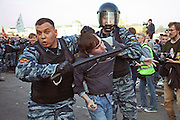 Moscow, Russia, 06/05/2012..A riot policeman strikes out at photographers while seizing a protestor by the hair as police arrest protestors at opposition demonstration against Russian Presidential election results on the eve of Vladimir Putins inauguration as President.