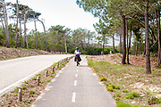 woman cycles on the Eurovelo 1 Atlantic coast route Near Nazare in central  Portugal. This cycling path runs along the Atlantic ocean