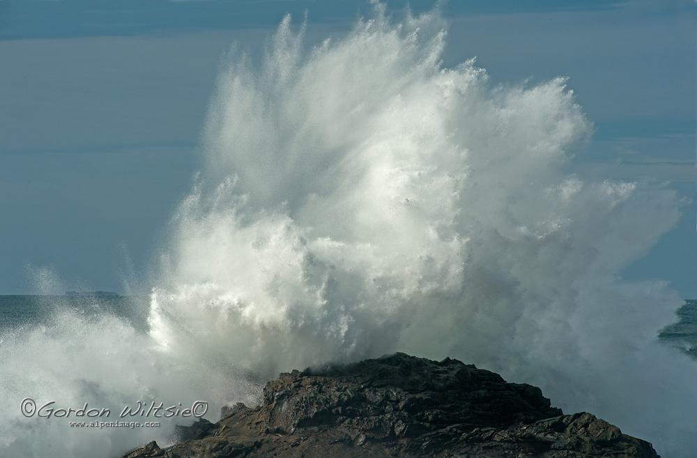 Pacific Ocean waves crash ashore at Bean Hollow State Beach near Pescadero, California.  A freighter bound for San Francisco sails on the horizon.