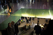 View from the escalators inside Tate Modern, London, UK. Visitors to the art gallery travel from floor to floor through the glass interior.