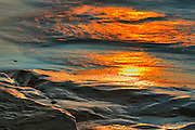 Waters of the Gulf of St. Lawrence lapping off the rocks at sunset
